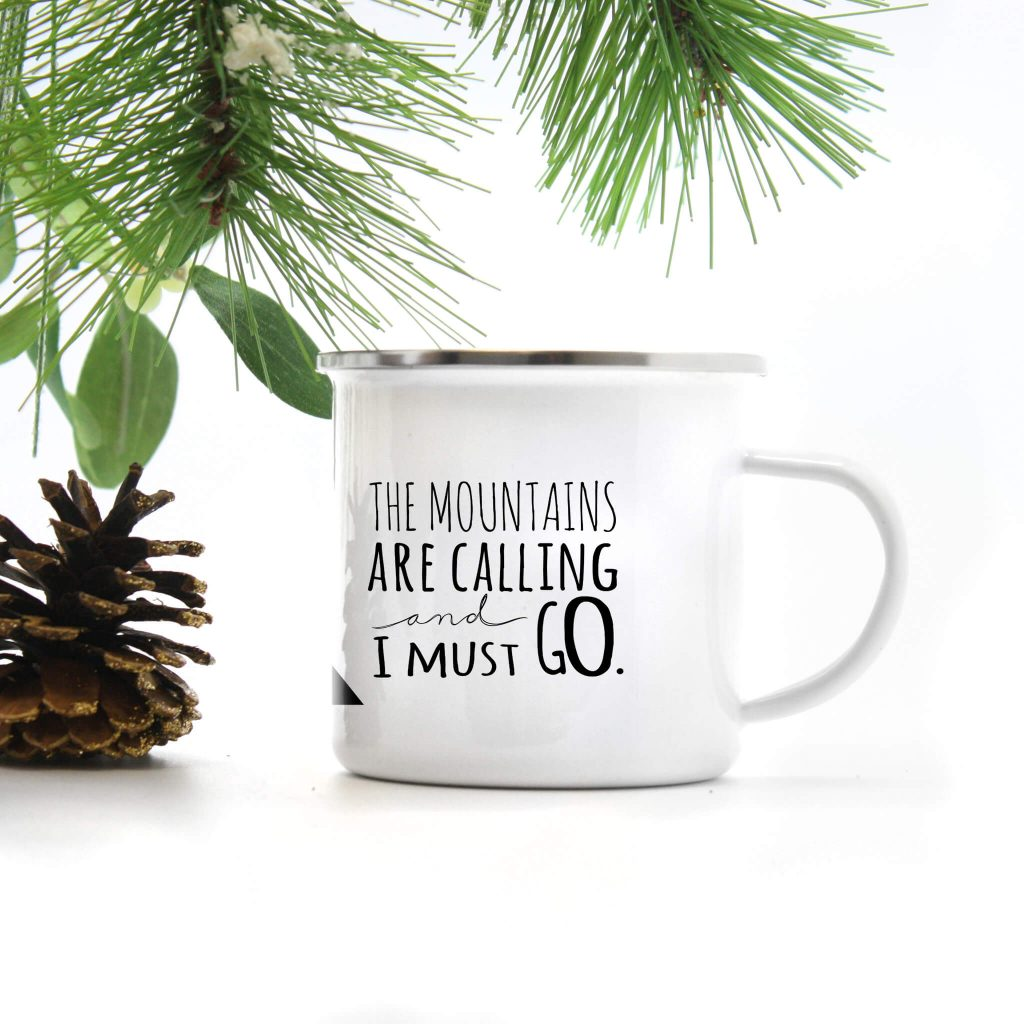 white enamel camp mug which reads the mountains are calling and I must go