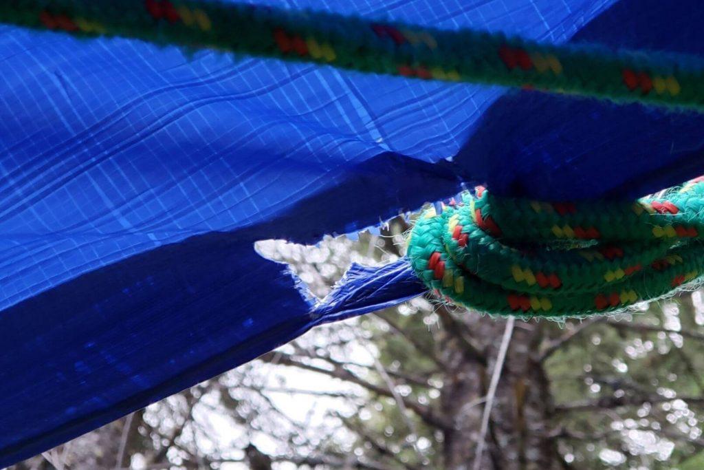 A rip in a blue camping tarp