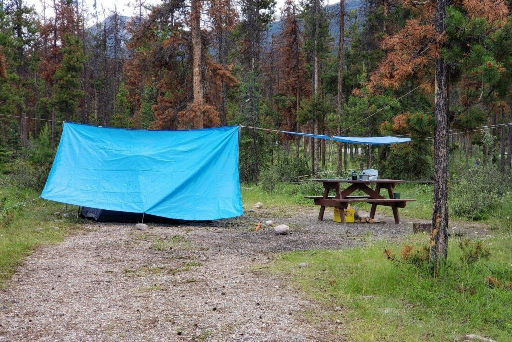 A campsite with a tarp hung over the tent and picnic table