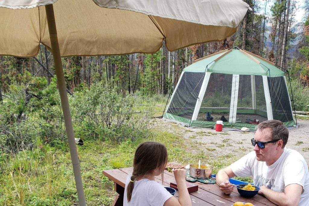 A patio umbrella being used at the campsite to keep rain off the picnic table