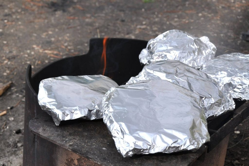foil packages cooking on a campfire
