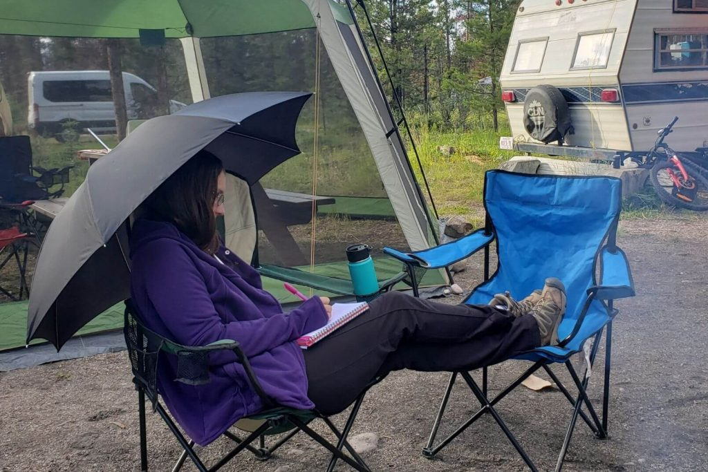 A woman sitting in a camping chair using an umbrella to stay dry at the campground