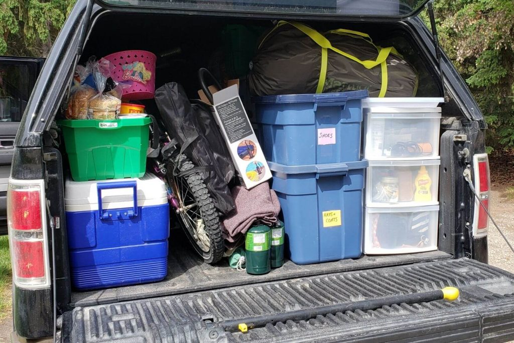 the back of a truck packed full with tubs and camping gear