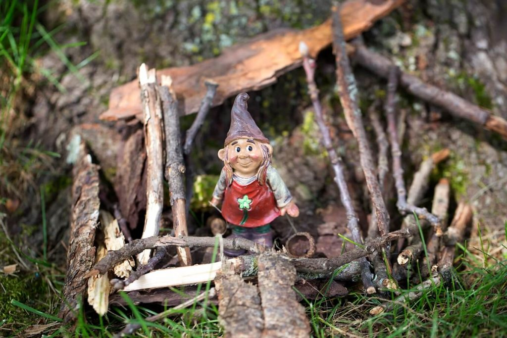 a little gnome sitting in a house of twigs and sticks