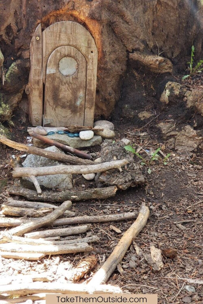 a wooden fairy door on a tree trunk with a pebble and stick walkway