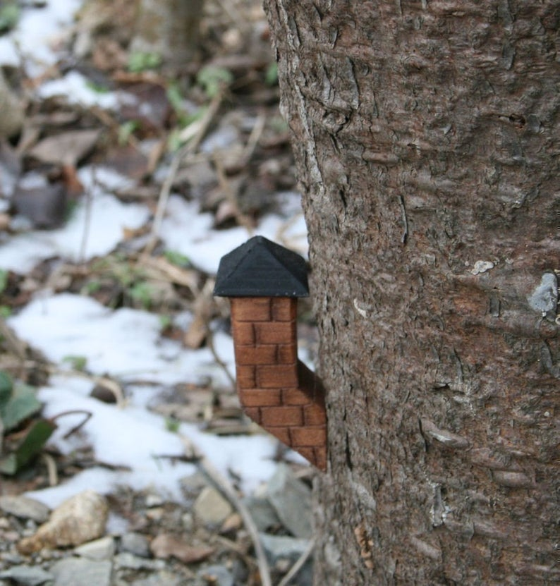 small fairy house chimney sticking out of a tree trunk