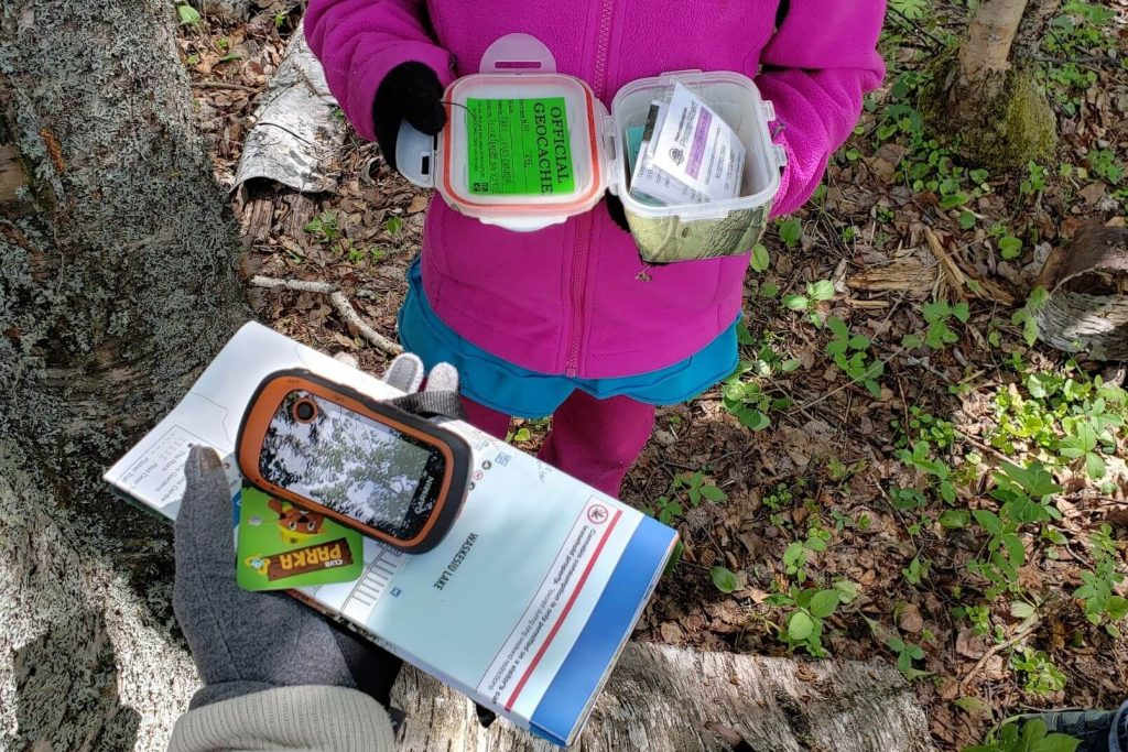 kids using a GPS and holding a geocache