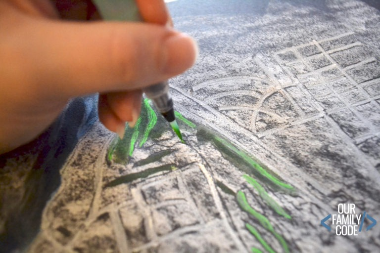 a hand using a green marker to add detail to a piece of map artwork