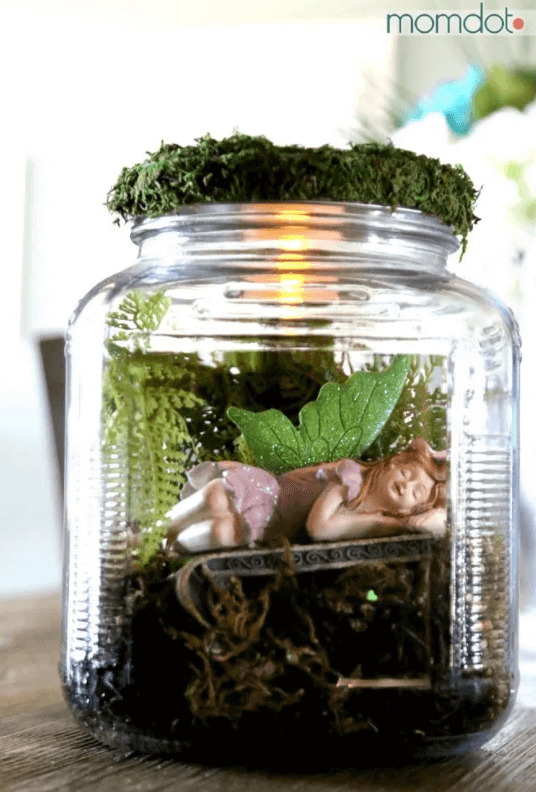 a small fairy sleeping in a moss filled mason jar