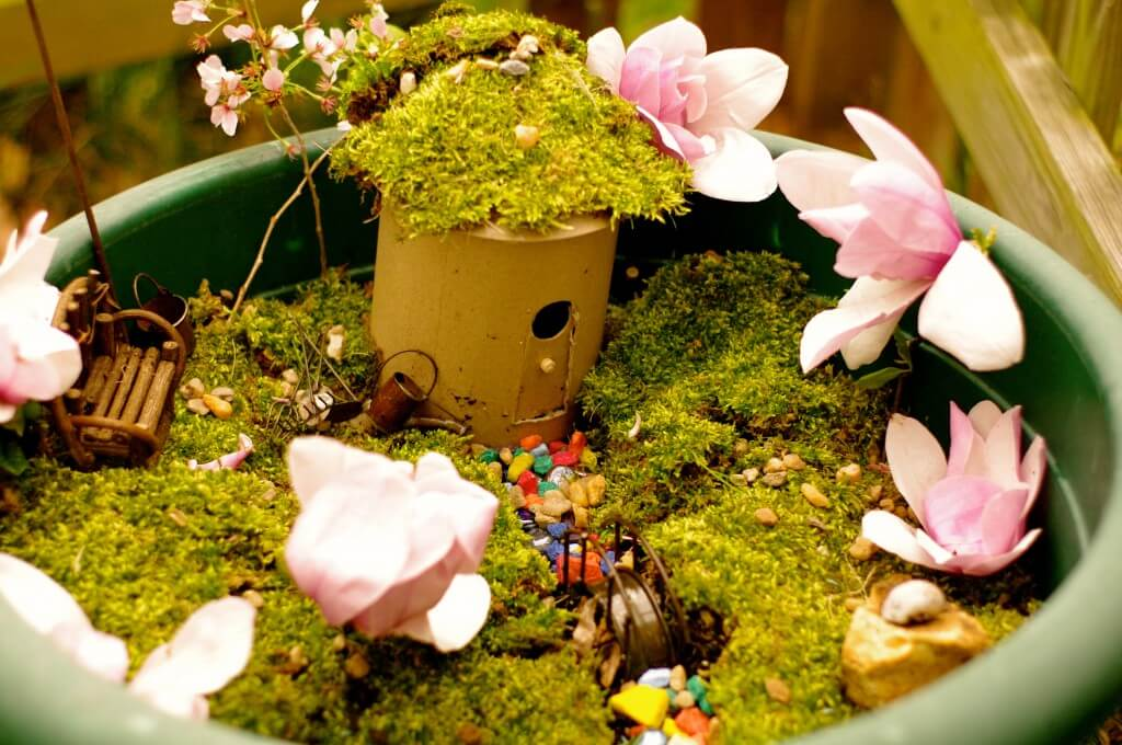 a fairy garden with moss, pebbles, and flowers