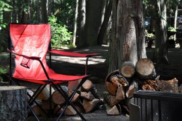 a red camping chair sitting by a pile of logs at a dark, wooded campsite