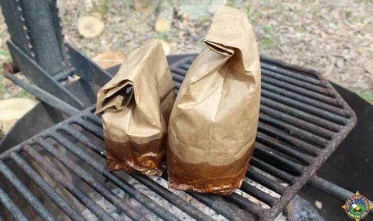 camping breakfast in a paper bag over the coals