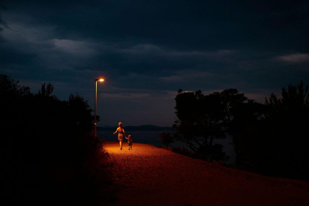 a mom and little girl walking down a dark city street