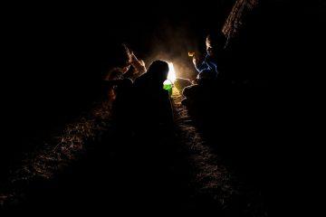 kids playing outside huddled around a lantern in the dark